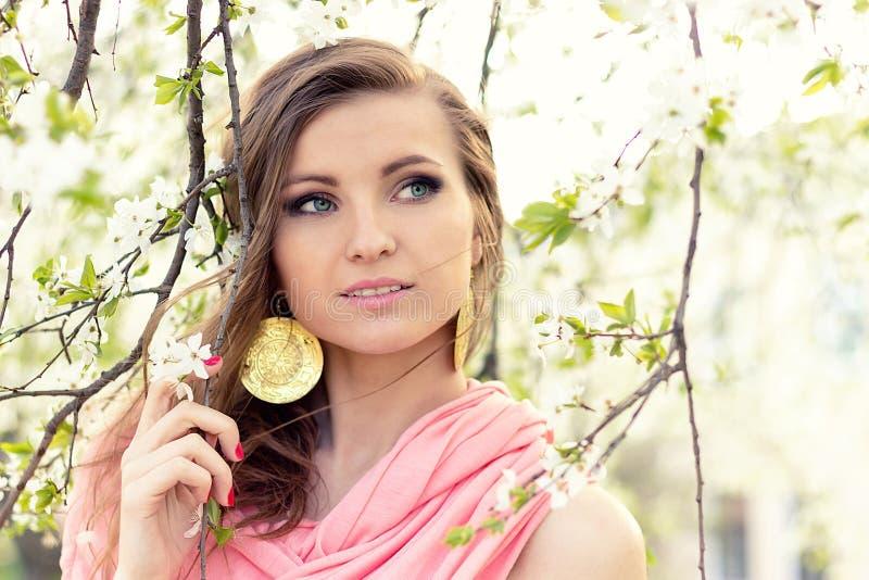 Menina elegante do querido bonito em um revestimento cor-de-rosa perto da árvore com as flores brancas com o vento em seu cabelo imagem de stock royalty free