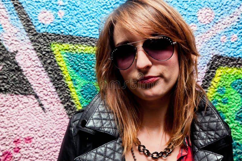 Menina elegante e parede colorida dos grafittis imagem de stock royalty free
