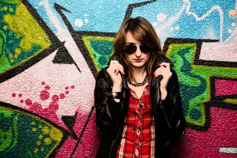 Menina elegante e parede colorida dos grafittis imagem de stock