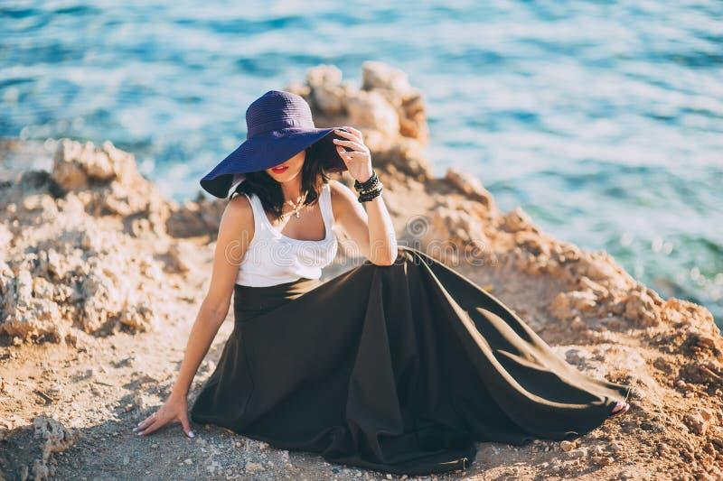 Menina elegante em um chapéu grande que levanta em uma rocha na praia imagens de stock royalty free
