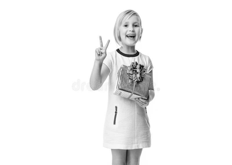 Menina elegante feliz no branco com o presente do Natal que mostra a vitória fotos de stock