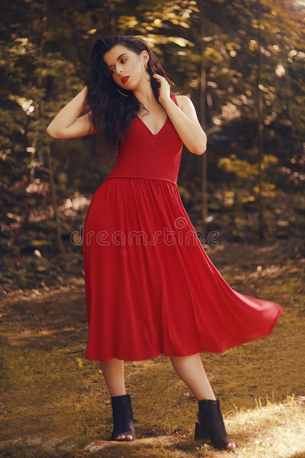 Menina elegante na mulher do moderno do parque ou da floresta com um vestido longo vermelho elegante Modelo moreno da beleza Meni imagem de stock
