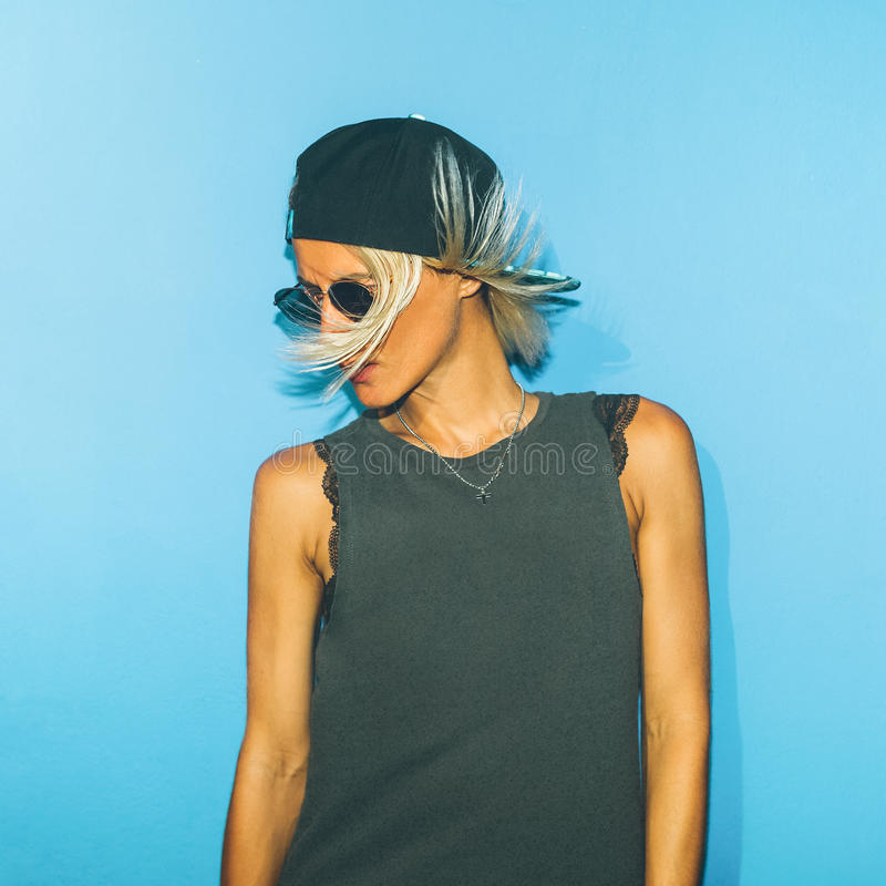 Menina elegante que está na parede azul em vidros à moda e na fotos de stock