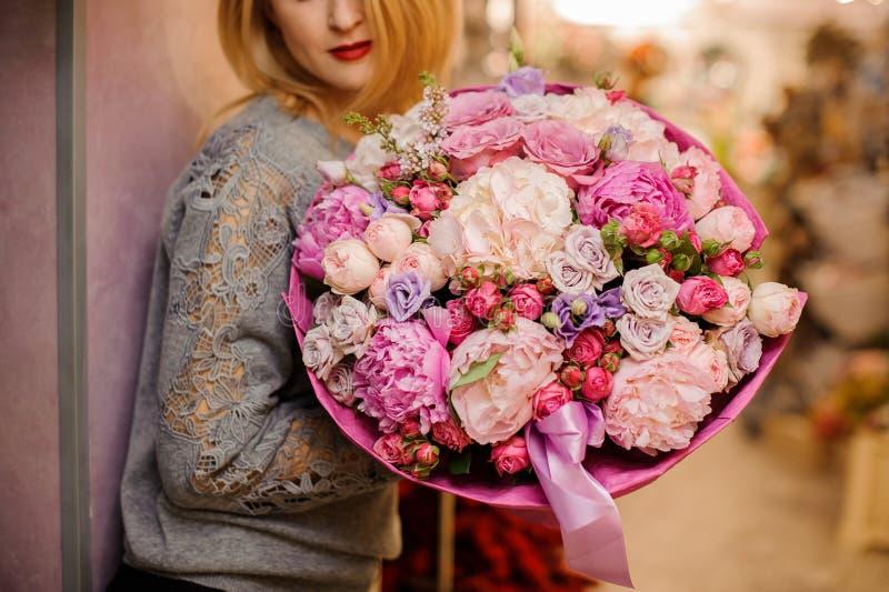 A menina elegante sorri posses um ramalhete enorme de flores cor-de-rosa e roxas diferentes fotos de stock