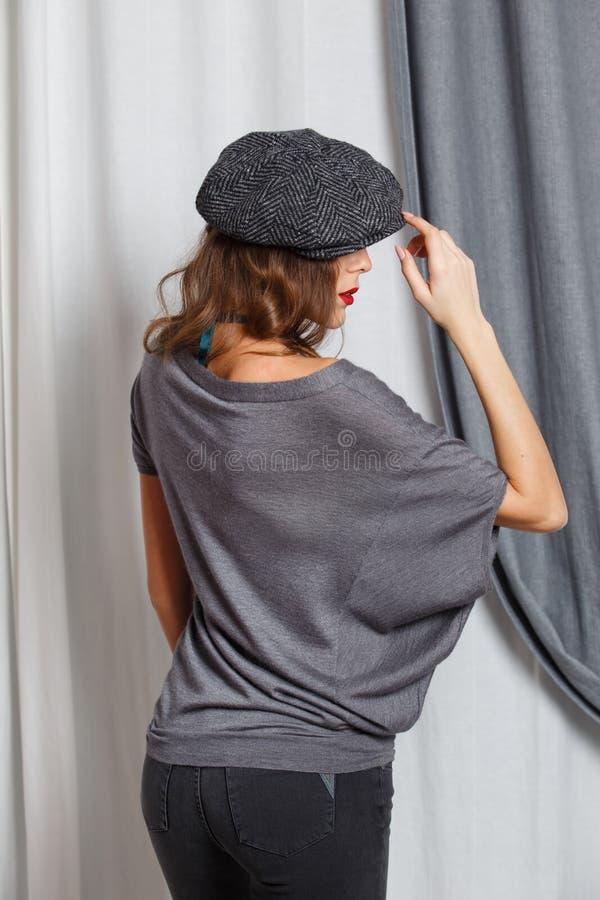 A menina elegante vestida em uma blusa cinzenta ? moda com gr?nulos verdes, as cal?as de brim cinzentas e um tamp?o ? moda levant fotografia de stock
