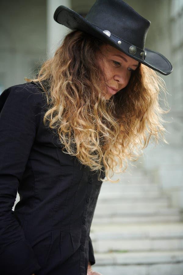 Menina elegante vestida na camisa preta, no chap?u e na cal?as larga levantando perto da casa branca velha fotos de stock