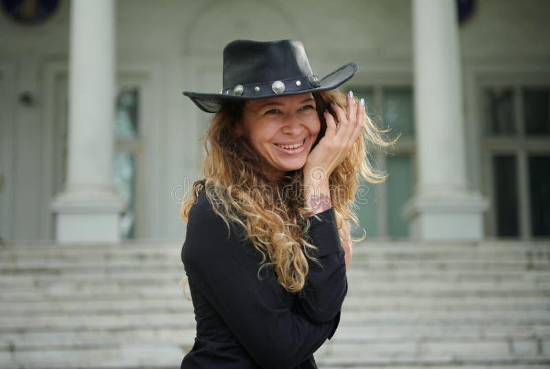 Menina elegante vestida na camisa preta, no chap?u e na cal?as larga levantando perto da casa branca velha foto de stock