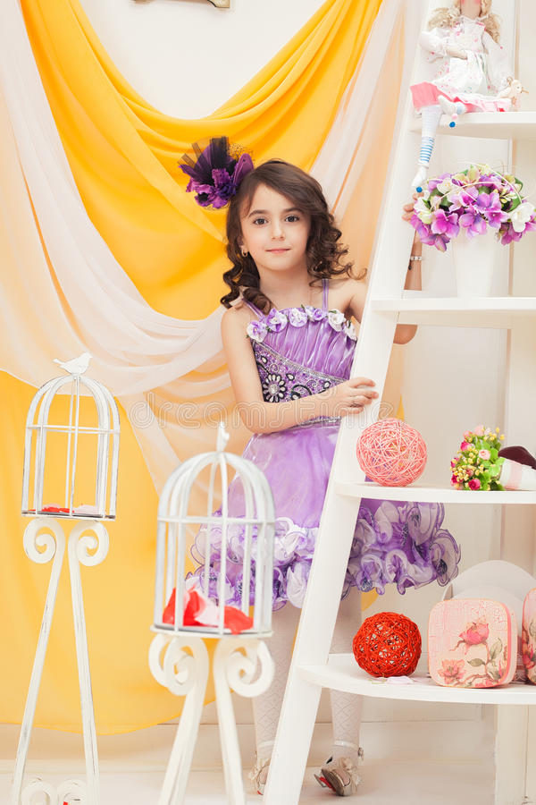 Menina elegantemente vestida que levanta no interior do vintage foto de stock