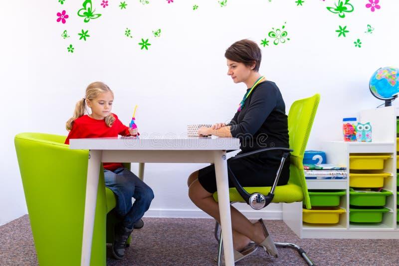 Menina elementar da idade na sessão de terapia ocupacional da criança que faz exercícios brincalhão com seu terapeuta imagens de stock