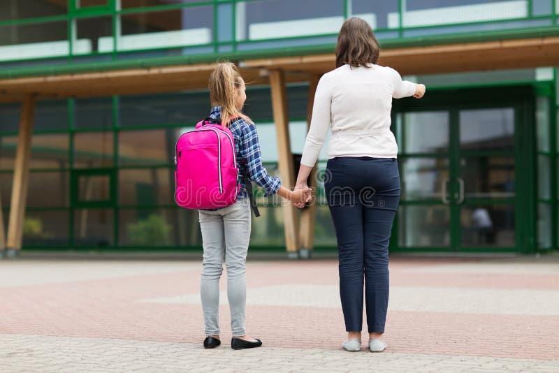 Menina elementar do estudante com a mãe na jarda de escola fotografia de stock