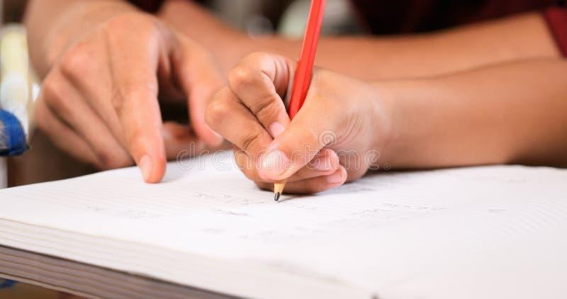 Menina elementar que faz a escrita da mão dos trabalhos de casa no livro de exercício fotografia de stock