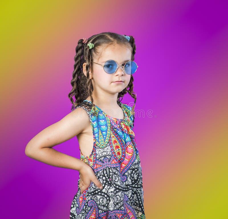 Menina em óculos de sol azuis no fundo do arco-íris fotografia de stock royalty free