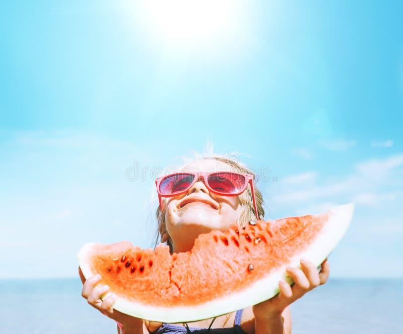 Menina em óculos de sol cor-de-rosa com o retrato engraçado do segmento grande da melancia Imagem saudável do conceito comer fotos de stock royalty free
