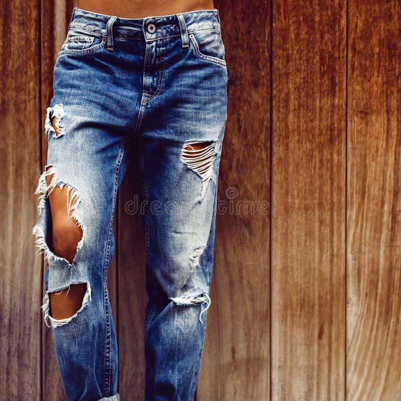 Menina em calças de brim rasgadas à moda no fundo de madeira imagens de stock
