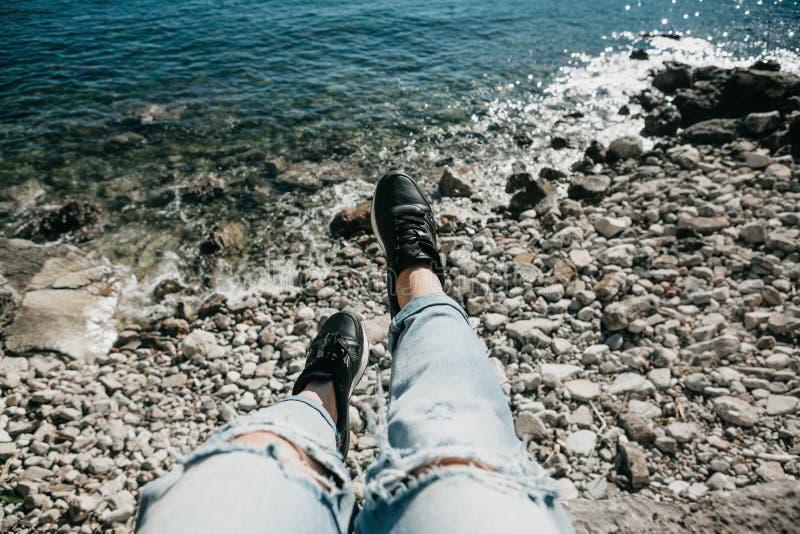 A menina em calças de brim rasgadas elegantes e em sapatilhas senta-se na praia e nos restos imagem de stock royalty free