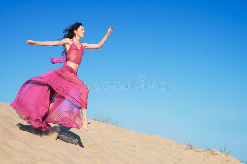 A menina em carmesins pairosos veste o corredor em dunas de areia imagem de stock royalty free
