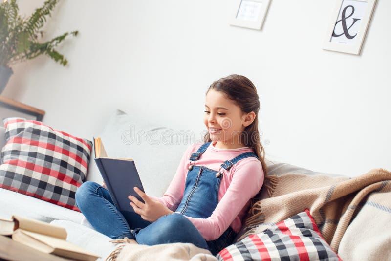 Menina em casa que senta o sorriso do livro de leitura alegre imagem de stock royalty free