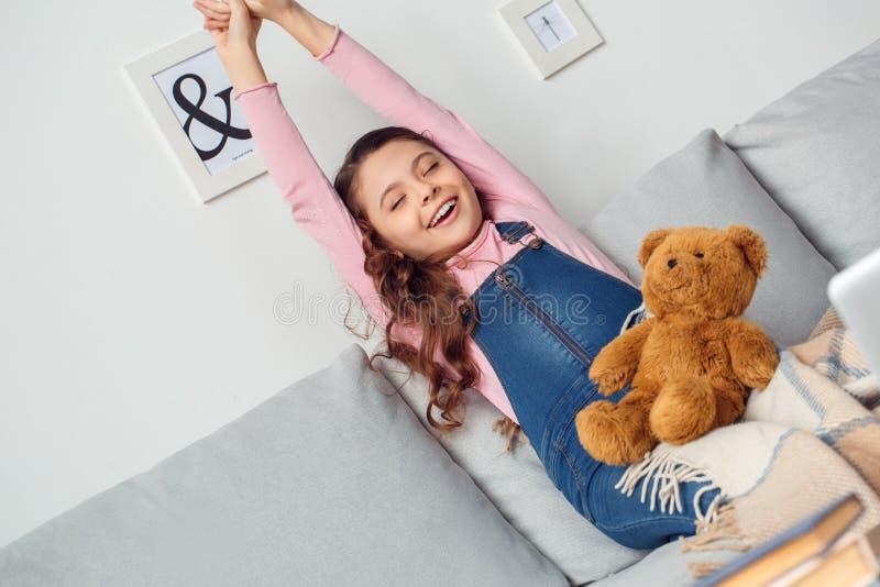Menina em casa que senta-se esticando o sorriso das mãos feliz imagens de stock royalty free