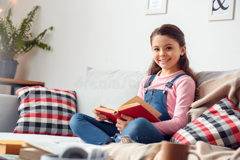 Menina em casa que senta-se mantendo o livro que olha a câmera feliz foto de stock royalty free