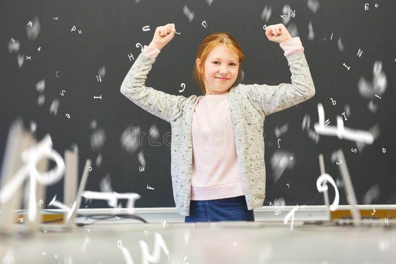 Menina em elogios da escola primária na frente do quadro-negro foto de stock royalty free