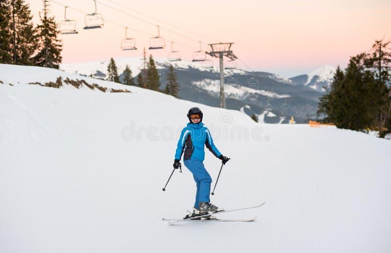 Menina em esquis na neve macia nas montanhas imagens de stock royalty free