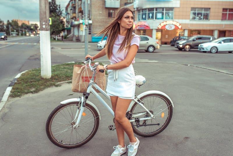 A menina em estradas transversaas da cidade do verão, em suportes com bicicleta e em pacote Esperando uma estrada livre para ir M imagens de stock