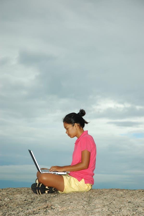 Menina em férias usando o computador portátil fora imagens de stock royalty free