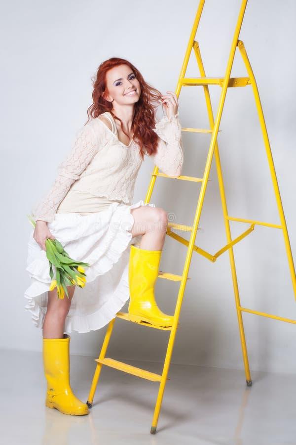 Menina em gumbooots amarelos imagem de stock