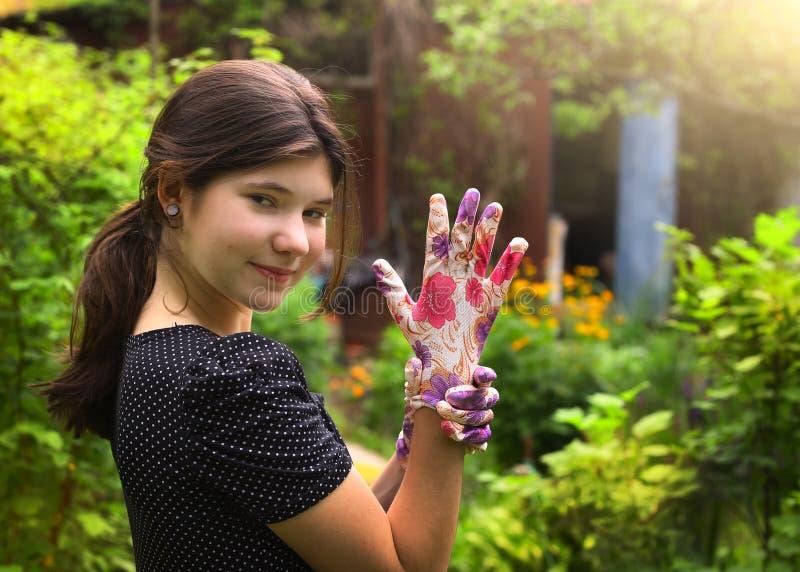 A menina em luvas do vestido e do jardim do às bolinhas no verão esverdeia o fundo do país fotografia de stock royalty free