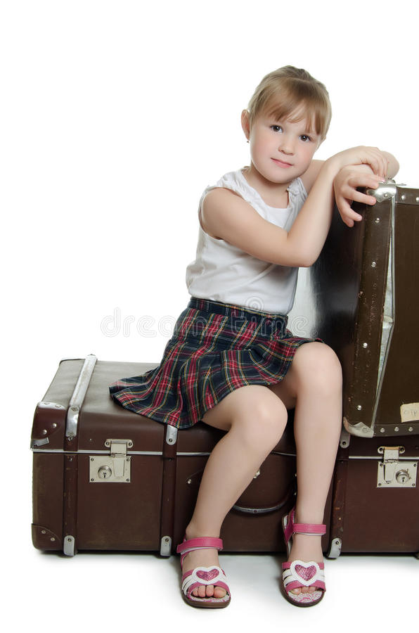A menina em malas de viagem velhas imagens de stock
