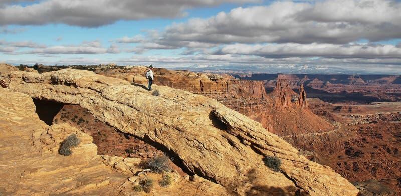 Menina em Mesa Arch no parque nacional de Canyonlands fotografia de stock