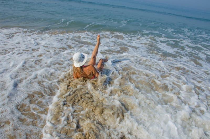A menina em nadadas de um chapéu no mar nas ondas imagem de stock