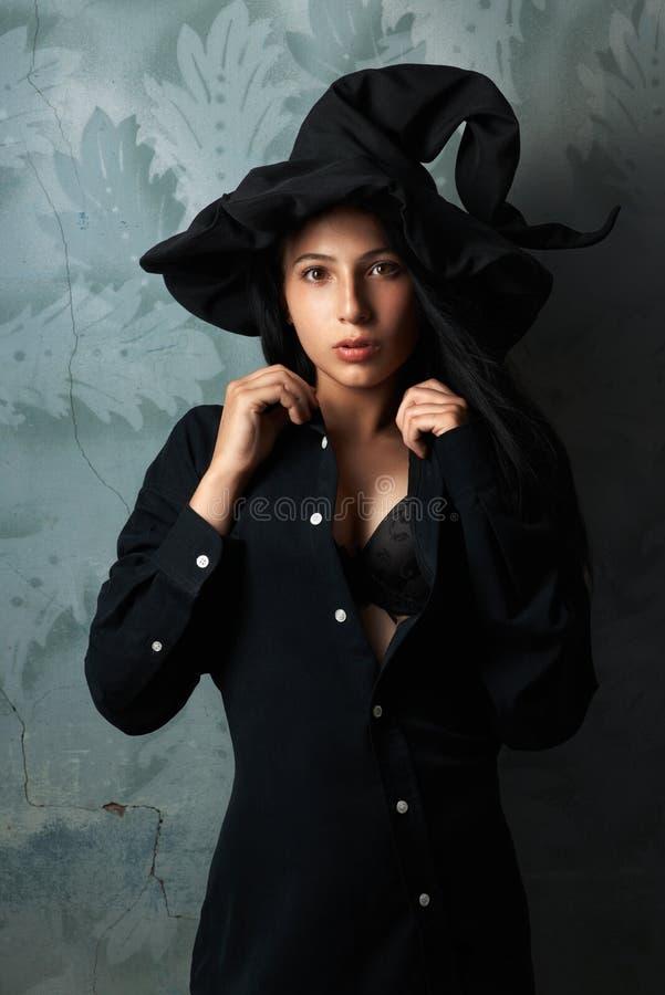 Menina em olhares 'sexy' de um traje da bruxa fotos de stock