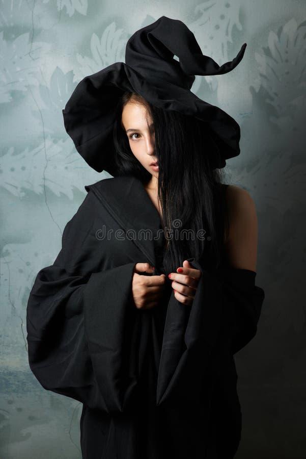 Menina em olhares 'sexy' de um traje da bruxa imagens de stock