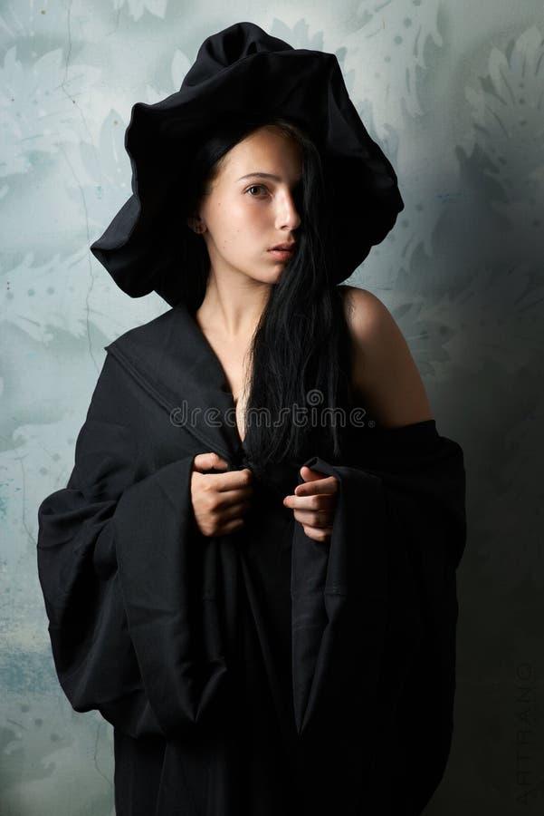 Menina em olhares 'sexy' de um traje da bruxa fotografia de stock royalty free