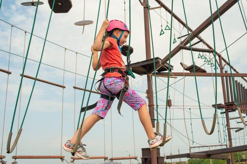 A menina em passagens protetoras e da segurança da roupa sobre uma ponte de suspensão no esportes estaciona, guardando as cordas  fotos de stock