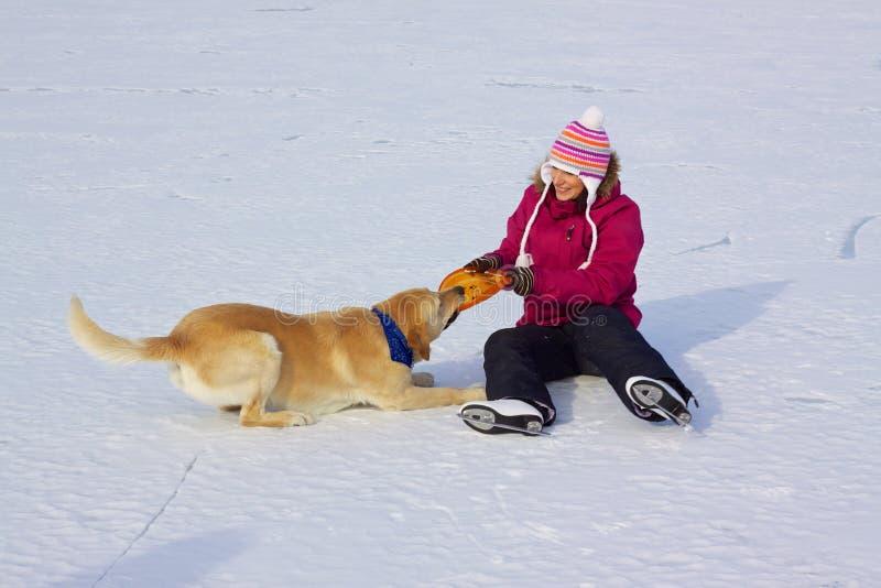 Menina em patins de gelo com cão foto de stock