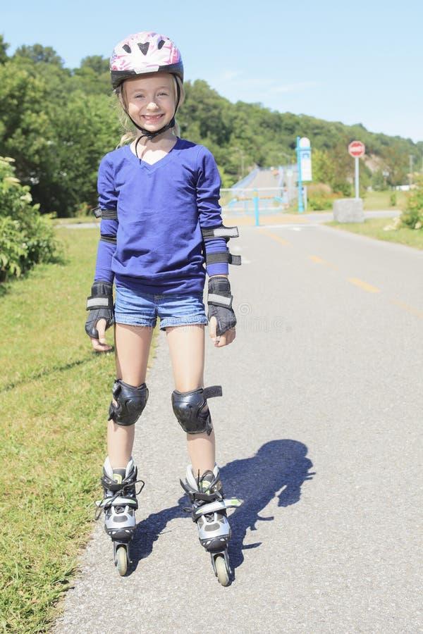 Menina em patins de rolo em um parque foto de stock royalty free