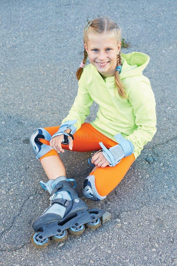 Menina em patins de rolo no parque Menina feliz foto de stock royalty free