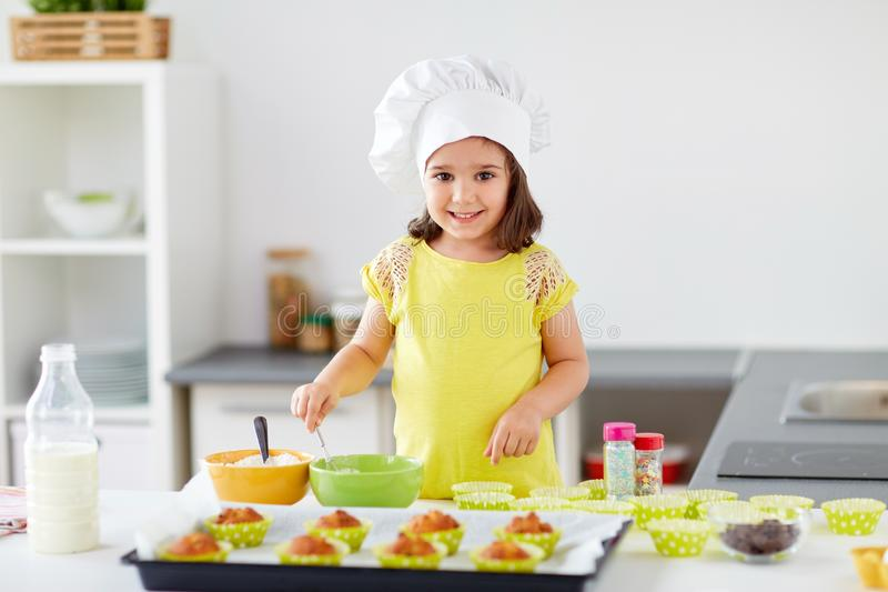 Menina em queques do cozimento do toque dos cozinheiros chefe em casa fotografia de stock