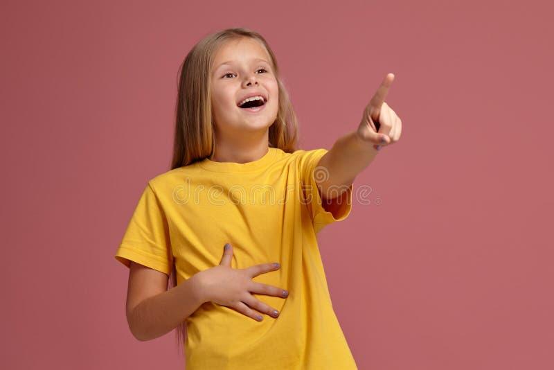 Menina em risos amarelos do t-shirt que aponta o dedo imagens de stock