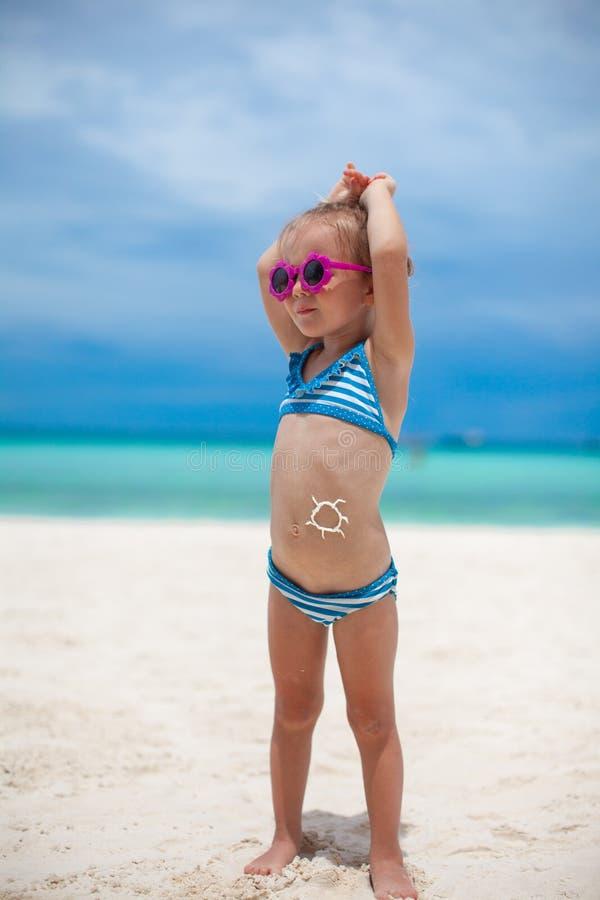A menina em seu estômago pintou um sorriso pelo sol imagens de stock
