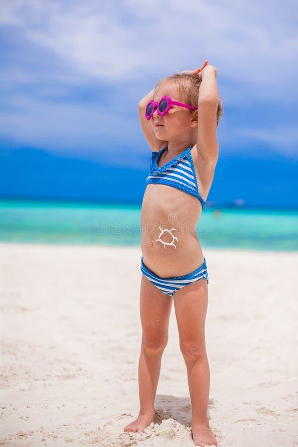 A menina em seu estômago pintou um sorriso pelo sol foto de stock