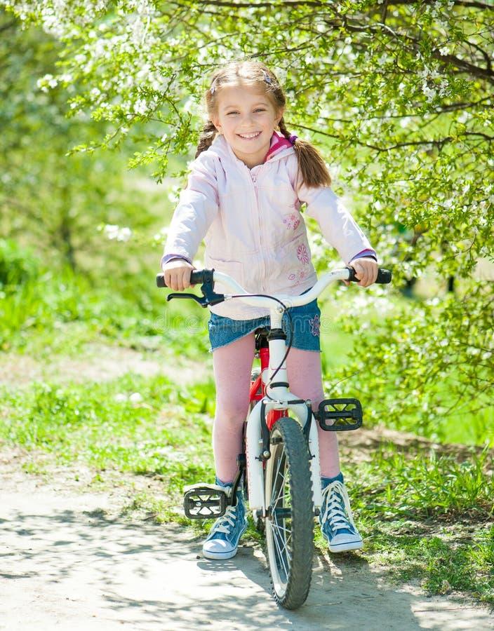 Menina em sua bicicleta imagens de stock