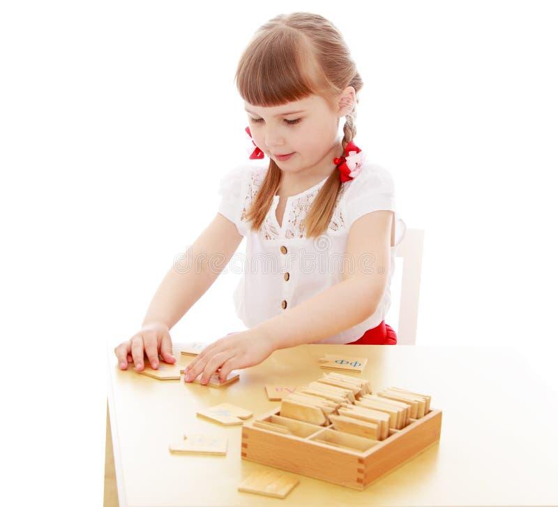Menina em um ambiente de Montessori imagem de stock