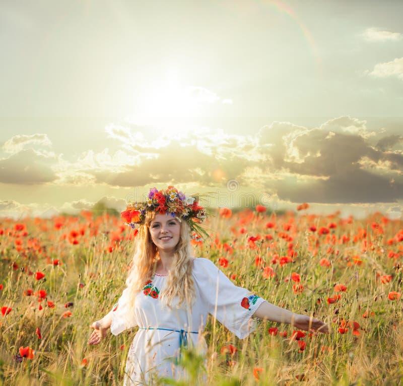 Menina em um campo da papoila fotografia de stock royalty free