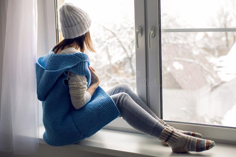 A menina em um chapéu branco e em uma veste azul está sentando-se fotografia de stock royalty free