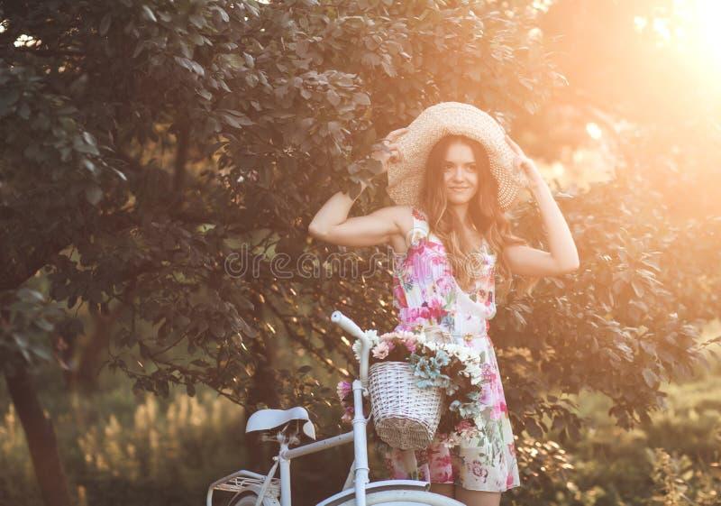 Menina em um chapéu com uma bicicleta imagens de stock
