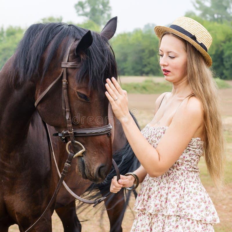 Menina em um chapéu de palha com um cavalo fotografia de stock royalty free