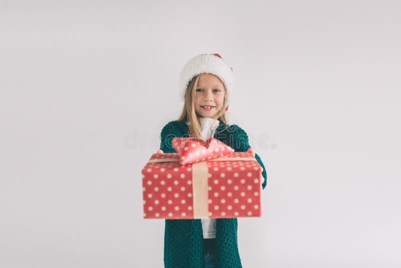 Menina em um chapéu do Natal que guarda presentes no fundo branco Nós desejamos-lhe o Feliz Natal e um ano novo feliz imagens de stock